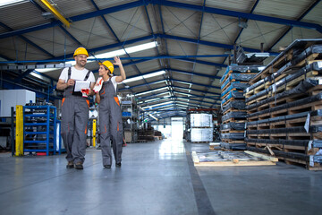 Factory workers in work wear and yellow helmets walking through industrial production hall and discussing about organization.