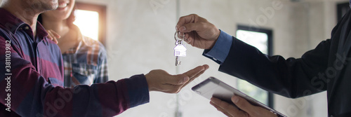 Fotografie, Obraz Bank agent give key of apartment or resident to young couple after successful di