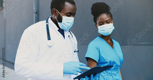 African American couple, man and woman, doctors colleagues in medical masks walking, talking and using tablet device Fototapeta