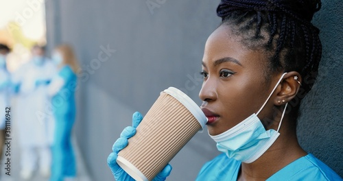 Obraz na plátně Tired young African American woman doctor taking off medical mask and sipping hot drink while resting and leaning on wall with eyes closed