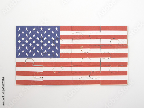 Fototapeta Jigsaw puzzle with picture of American flag put together in front of white background obraz na płótnie