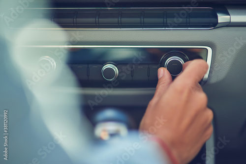 Listening music, cropped shot of a woman turning on radio while driving in the city, close up