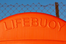 The Word Lifebuoy On An Orange Container That Hold A Life Ring