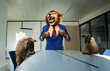 canvas print picture Angry boss lion in the suit with sheep employees stand and tear shirt using paws near desk roaring, business concept