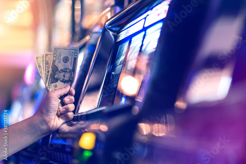 Fototapeta Slot Machine Play Time. Female Gambler Hand hold money bill ready to win the game with one best shot casino close up obraz