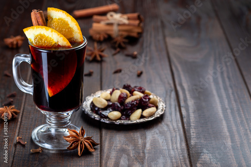 Fotomural Red glogg or mulled wine with orange slices and cinnamon stick on dark wooden ba