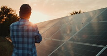 Owner Looks At Solar Power Plant Panels At Sunset
