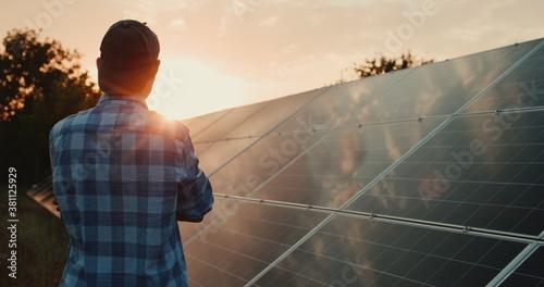 Fotografiet Owner looks at solar power plant panels at sunset