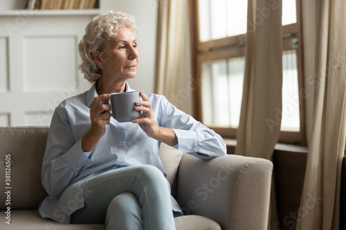 Obraz Time for good memories. Pleasant lonely older woman resting on sofa in living room drinking tea or coffee, pensive looking aside remembering life, thinking of current events, enjoying serenity at home - fototapety do salonu