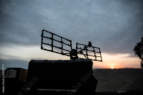 Papel de parede Silhouette of mobile air defence truck with radar antenna during sunset