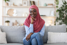 Joyful Young African Muslim Woman In Hijab Posing On Couch At Home