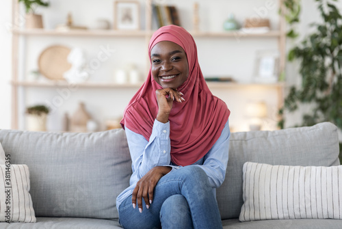 Fotografie, Obraz Joyful young african muslim woman in hijab posing on couch at home