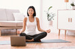 Millennial woman meditating with trainer online on laptop