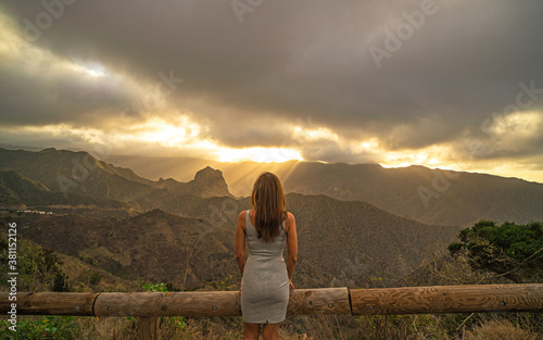 Cuadros en Lienzo woman from behind watching the sunset on a cliff