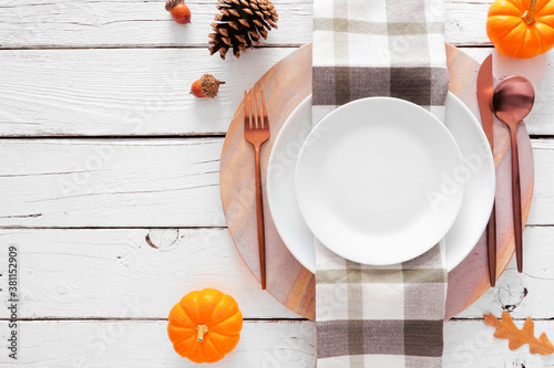 Obraz Autumn harvest or thanksgiving dinner table setting with plate, flatware, check print napkin, pumpkins and decor. Top view on a white wood background. - fototapety do salonu