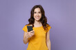 Smiling attractive young brunette woman 20s wearing basic yellow t-shirt posing using mobile cell phone typing sms message looking camera isolated on pastel violet colour background, studio portrait.