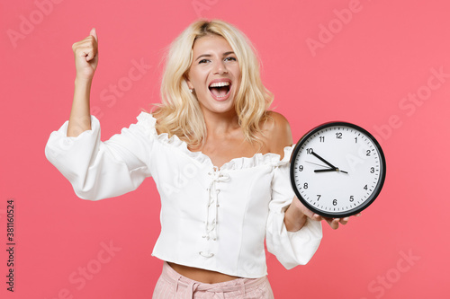 Fototapeta Excited happy joyful young blonde woman 20s wearing white casual clothes standing holding in hand clock doing winner gesture looking camera isolated on bright pink colour background, studio portrait. obraz