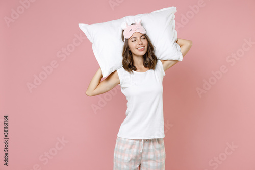 Smiling young woman in pajamas home wear sleep mask holding pillow behind head keeping eyes closed while resting at home isolated on pink background studio portrait. Relax good mood lifestyle concept.
