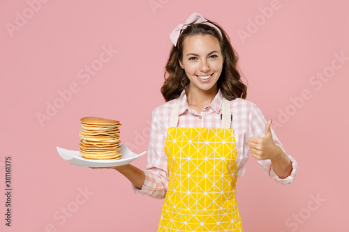 Smiling young brunette woman housewife 20s in yellow apron hold plate with pancakes showing thumb up while doing housework isolated on pastel pink background studio portrait. Housekeeping concept.