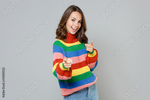 Fototapeta Smiling cheerful beautiful attractive young brunette woman 20s wearing casual colorful knitted sweater standing pointing index finger on camera isolated on grey colour background, studio portrait. obraz