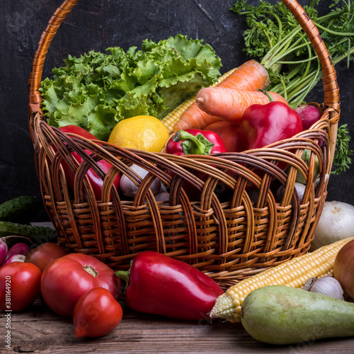 Fresh vegetables and fruits in basket on rustic wooden table
