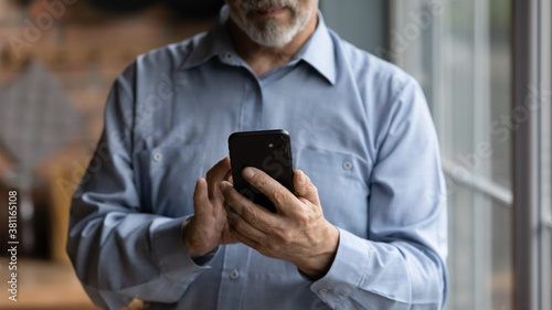 Fototapeta Crop close up of mature Caucasian grandfather hold modern smartphone gadget browse wireless internet. Senior man look at cellphone screen, read news online on device. Elderly and technology concept. obraz