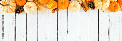 Fototapeta Autumn top border of pumpkins and fall decor. Overhead view on a rustic white wood banner background with copy space. obraz