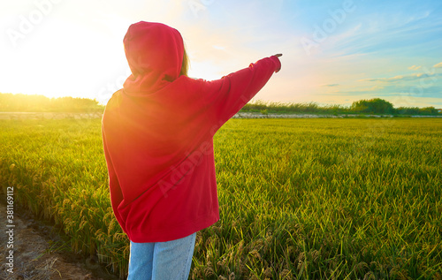 Fototapeta Young girl in red jacket pointing to infinity in a rice field at sunset time