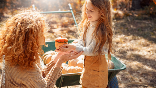 Tableau sur Toile Mother and little daughter holding pumpkin in hands, standing near wheelbarrow