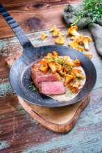 Fried Dry Aged Wagyu Roast Beef Steak With Chanterelle In Cream Sauce Offered As Close-up In A Rustic Wrought-iron Skillet