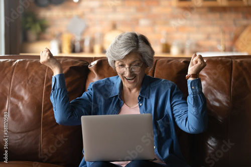 Overjoyed senior Caucasian grandmother in glasses relax on sofa at home triumph Wallpaper Mural