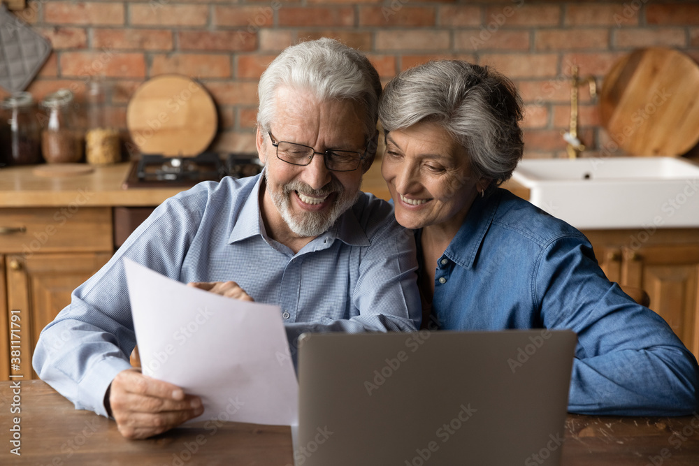 Obraz Happy elderly couple read postal paper document satisfied with banking health insurance contract or notice. Smiling mature man and woman consider good news in post paperwork letter correspondence. fototapeta, plakat