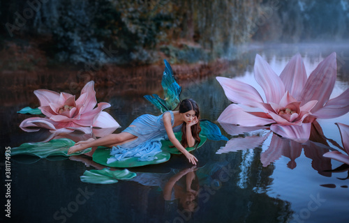 A beautiful woman a little cute fairy with butterfly wings lies on green water lily leaf Fototapeta