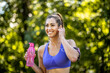 A young woman prepares to jog in nature, puts on headphones with music and carries a bottle of water with her and smiles