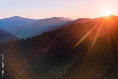Great view of colorful sunrise in the mountains backlight glow against the sunlight with sun flare and bokeh. Concept of the awakening wildlife, emotional experience in your soul. Retro effect. #381181745