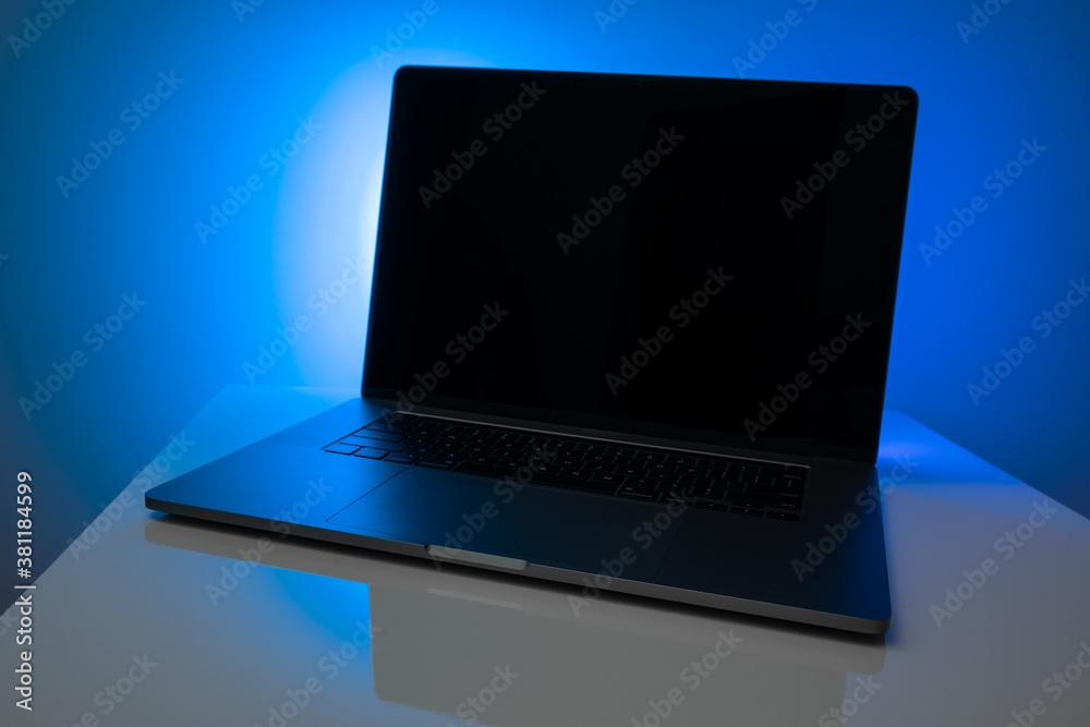 Fototapeta laptop in neon light on the table