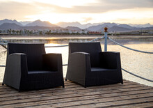 Two Empty Chairs On A Wooden Pier At Sunset