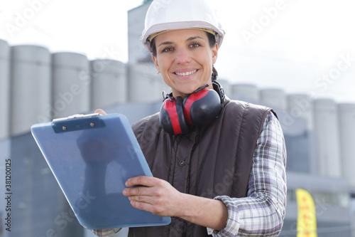 Fototapeta beautiful construction worker holding paper holder obraz