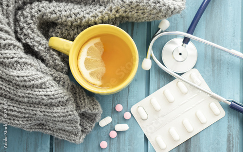 Fotografía Cold tea, pills, knitted scarf and stethoscope. Cold season.