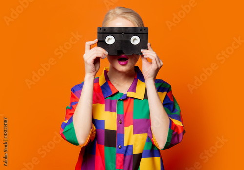 Fototapeta Style blonde in 90s clothes with VHS cassette