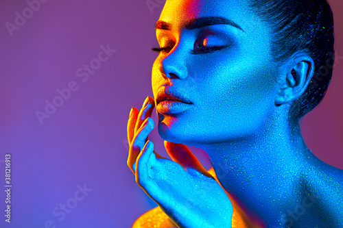 Fototapeta High Fashion model woman in colorful bright sparkles and neon lights. Beauty face, portrait of beautiful sexy girl, trendy glowing make-up. Art design colorful make up. Glitter Vivid neon makeup obraz