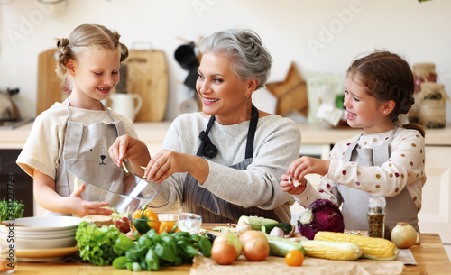 Mature woman with grandchildren preparing healthy food in kitchen Canvas Print