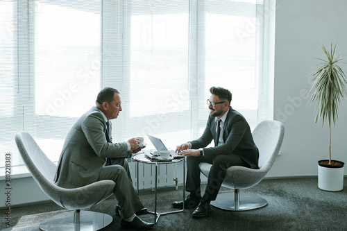Fototapeta Two confident mature businessmen in formalwear discussing working moments obraz