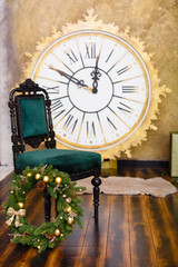 Christmas eve decoration with vintage clock. Time to New Year, interior with fer-tree, big clock, toys and soft armchair. Green & brown colors in wooden room.  Comfort home. Christmas presents