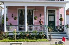 Close Up Front Porch View Of Galveston Island Pink Victorian House With Patio Furniture, Stone Bench, Flowering Bushes, Celling Fan, And Tall Windows With Lace Curtains.