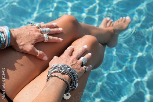 Fototapeta Mani con anelli su gambe con piedi in piscina obraz