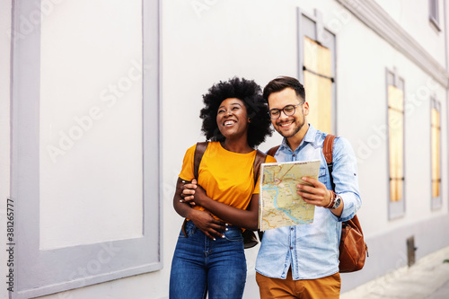Fototapeta Young attractive hipster multicultural couple walking downtown and looking at map. Tourism concept. obraz