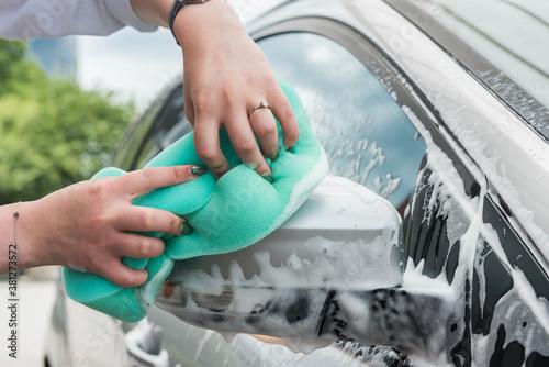 Tela girl washes a car with a washcloth with foam.