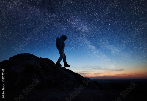 Photo Full length of astronaut walking down the mountain under beautiful night sky with stars