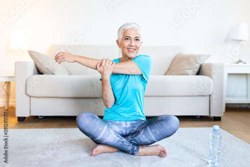 Foto Senior woman doing warmup workout at home
